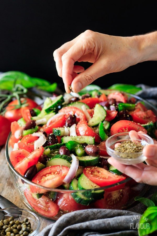 sprinkling dried oregano on Greek salad