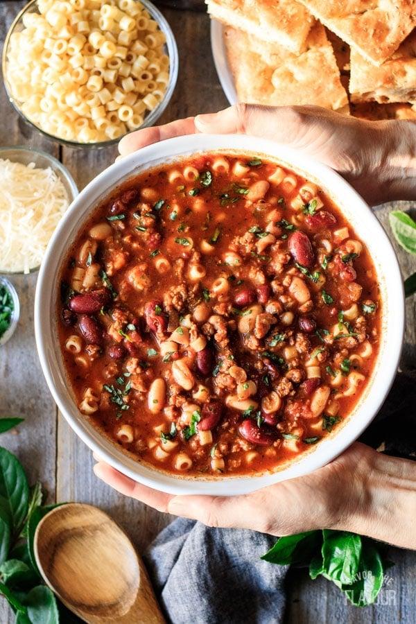 holding a bowl of pasta e fagioli soup