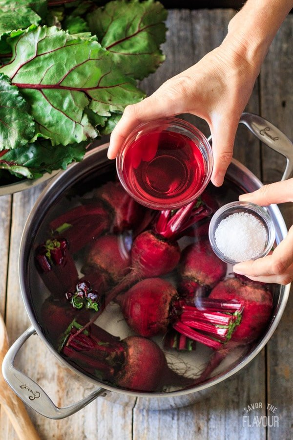 adding red wine vinegar and salt to the pot of beets