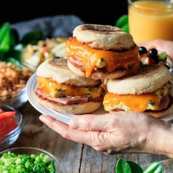 holding a plate of breakfast sandwiches