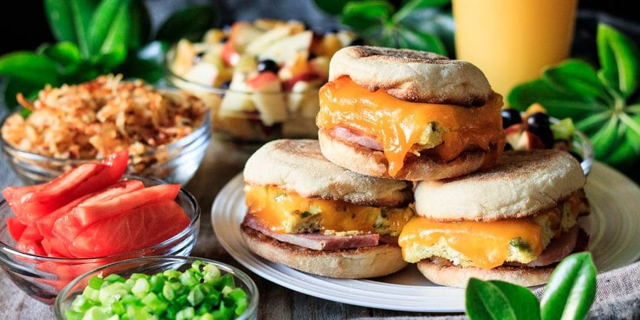 plate of breakfast sandwiches with hash browns, fruit salad, tomatoes, and orange juice