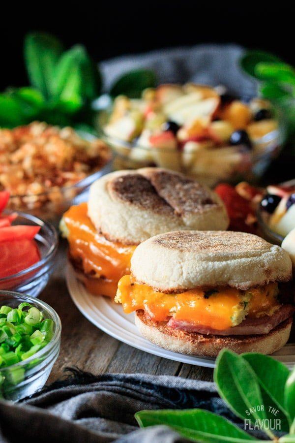 breakfast sandwiches on a plate with fruit salad, hash browns, tomatoes, and green onion