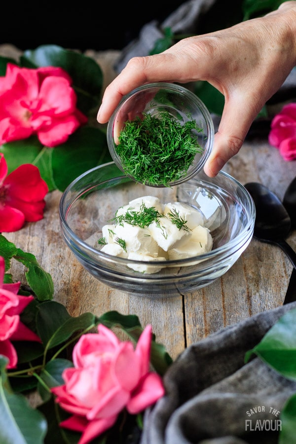 adding fresh dill to bowl of cream cheese