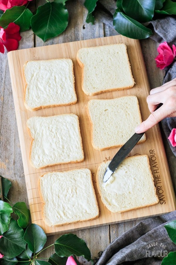 spreading butter on slices of white bread