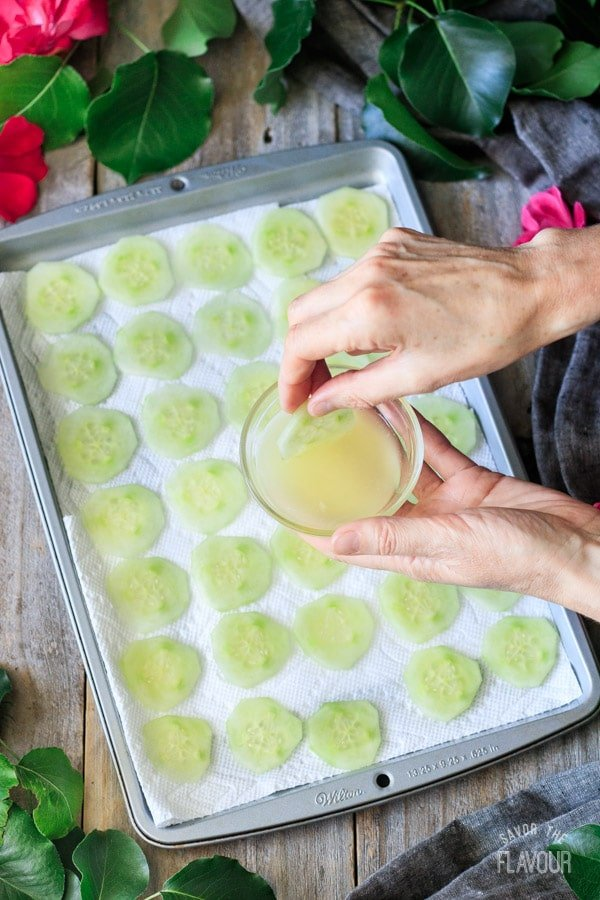 dipping the cucumber slices in lemon juice
