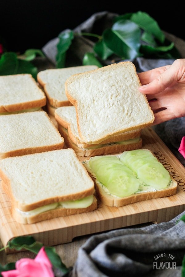 putting the top slice of bread on the cucumber sandwiches