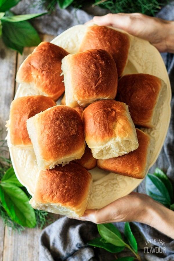 holding a plate of Hawaiian sweet rolls