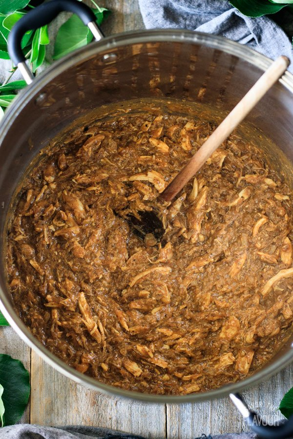 mixing shredded meat and seasonings in a large pot