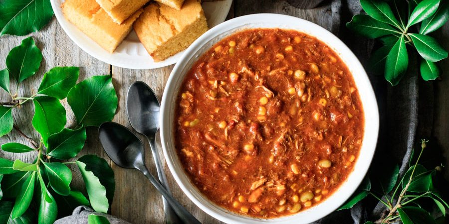 bowl of Brunswick stew with a plate of cornbread
