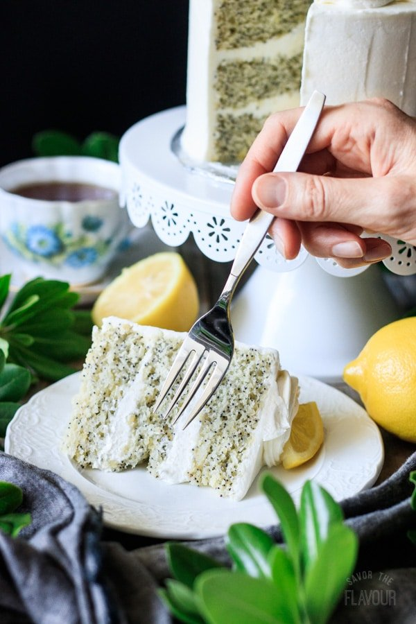 person holding a fork above lemon poppy seed cake