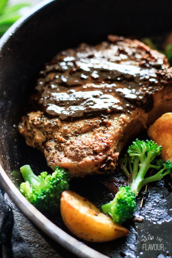 closeup of a pork chop in a cast iron skillet with veggies