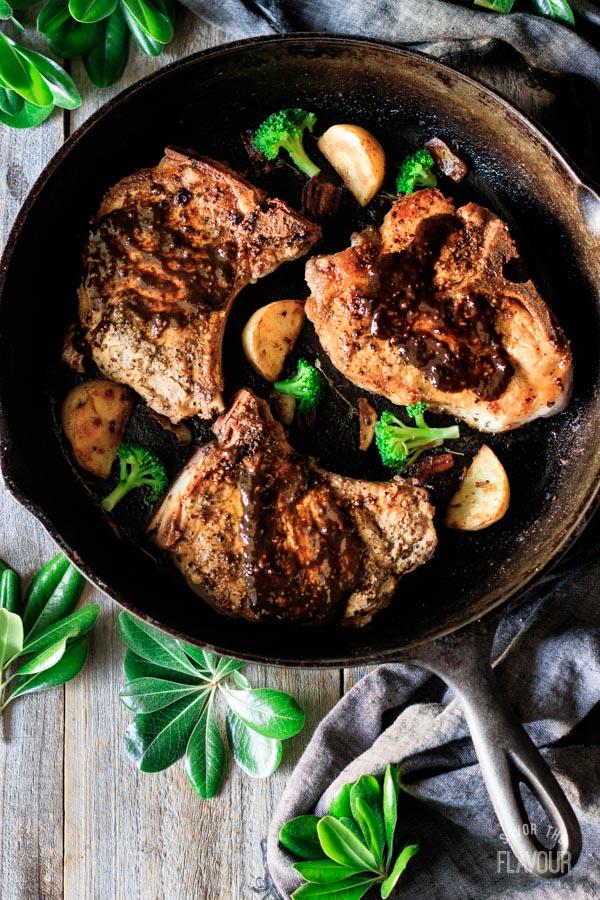 putting pan sauce on pork chops