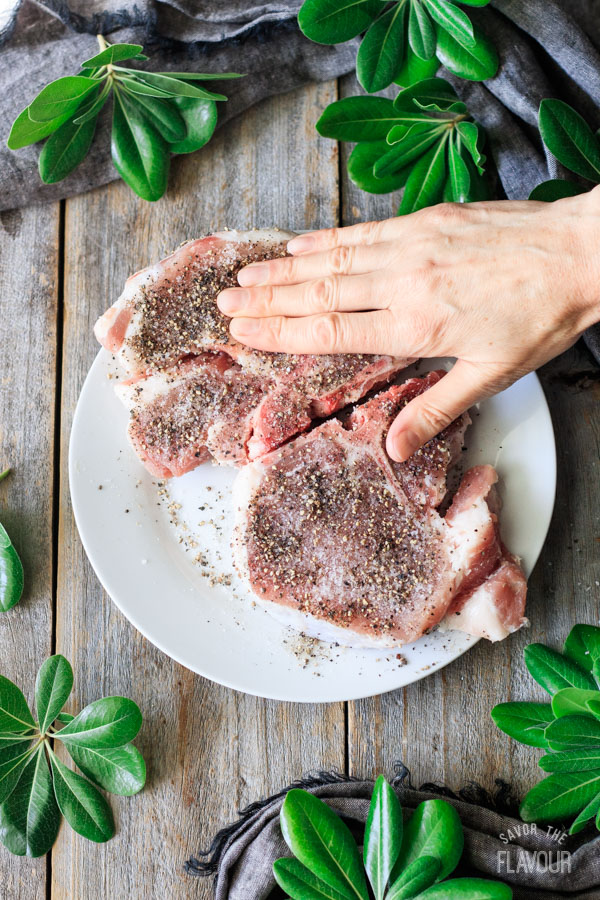 rubbing spices into pork chops