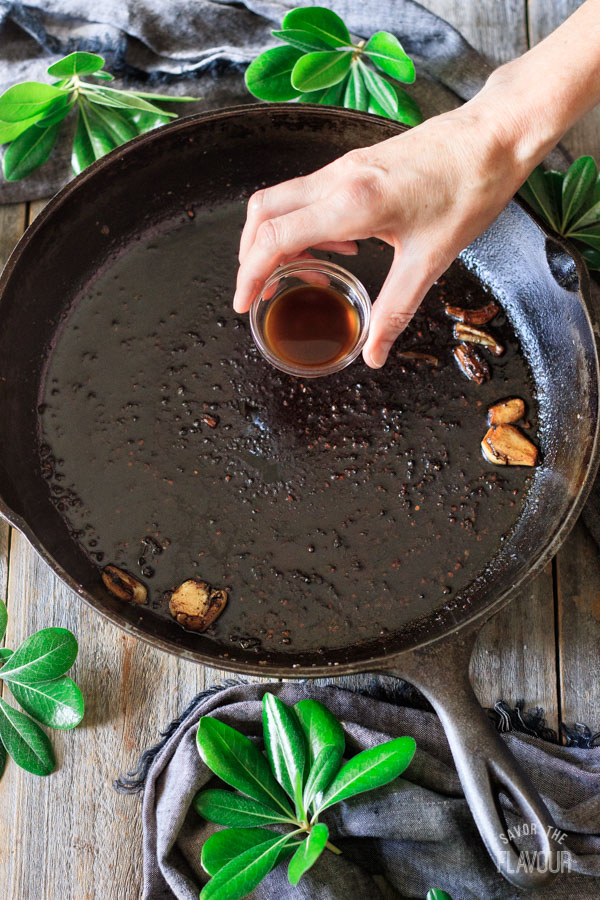 adding Worcestershire sauce to a cast iron skillet