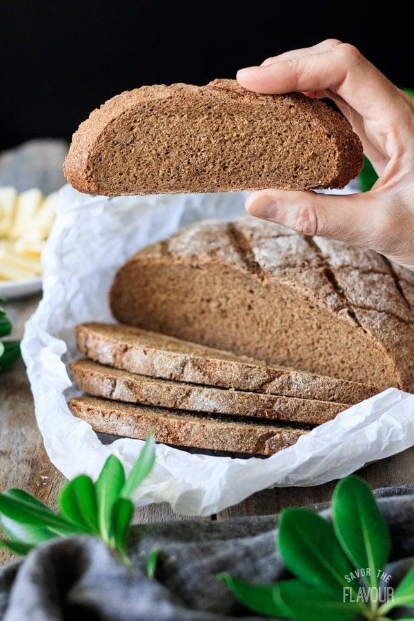 holding a slice of pumpernickel bread