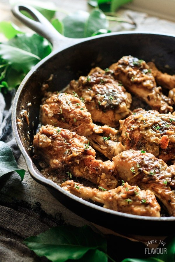 closeup of smothered chicken in a cast iron skillet