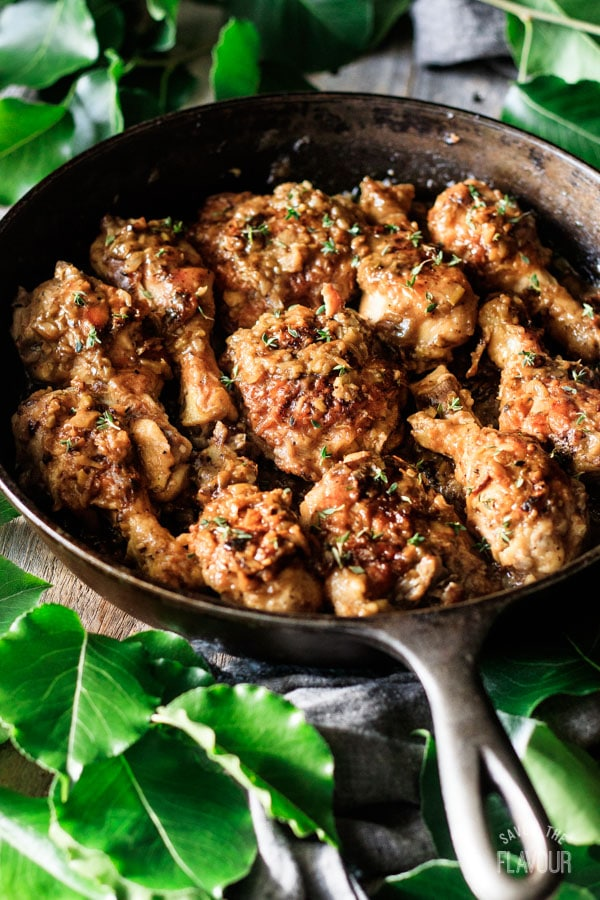 smothered chicken drumsticks and backs in cast iron skillet
