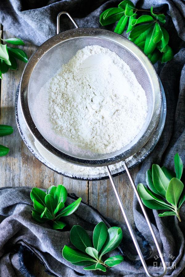 sifting flour and baking soda into a bowl