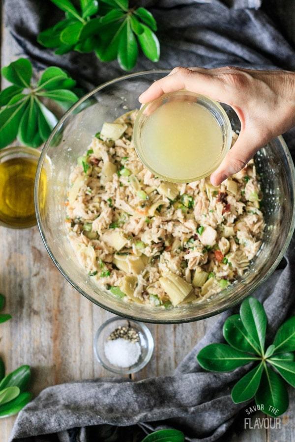 pouring lemon juice onto tuna salad