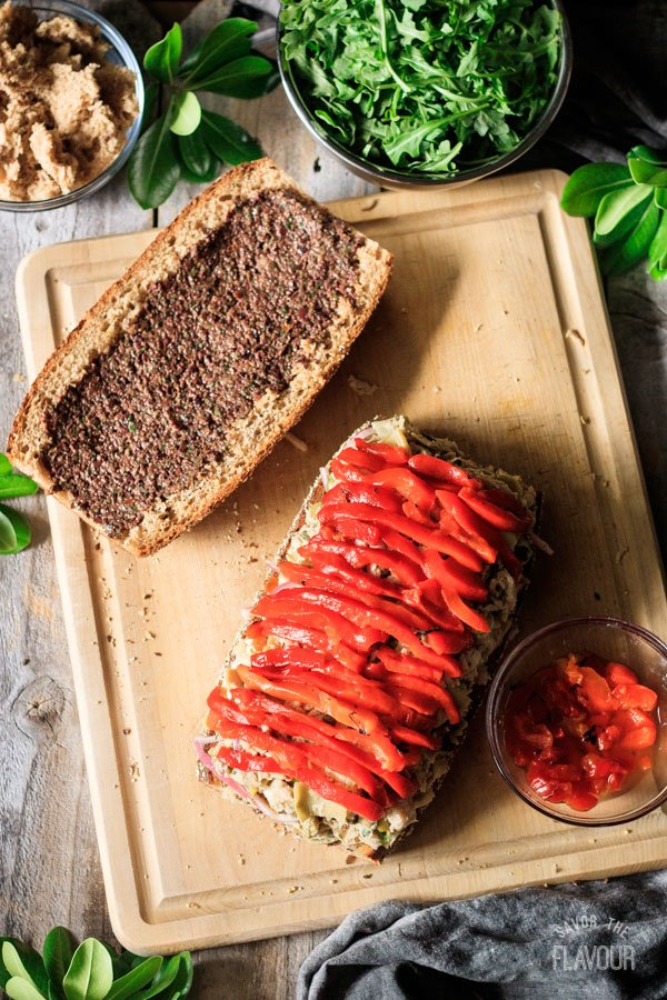 adding roasted red peppers to Sicilian tuna salad sandwich