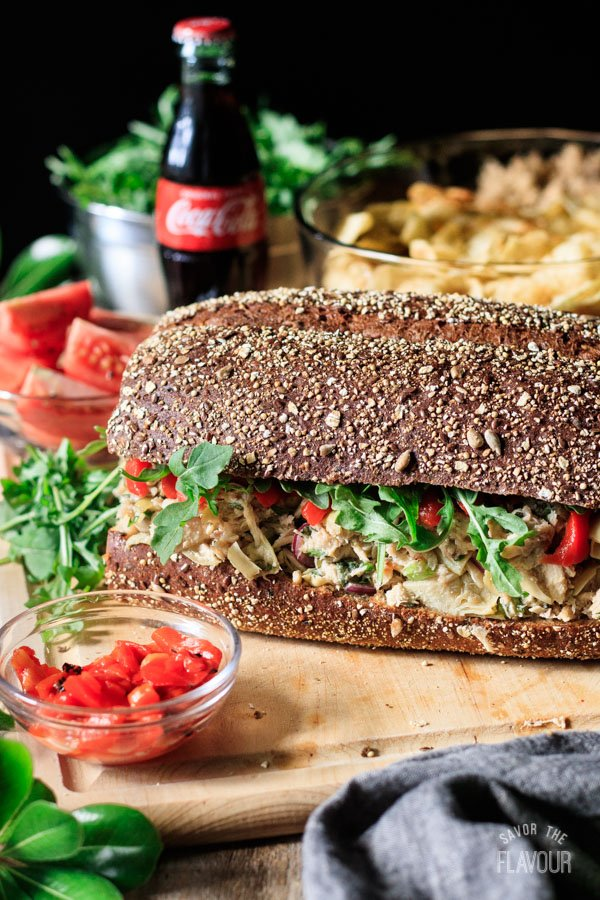 Sicilian tuna salad sandwich with tomatoes, chips, and Coke