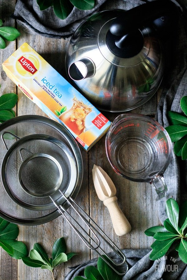 sieves, citrus reamer, measuring cup, tea bags, and electric kettle