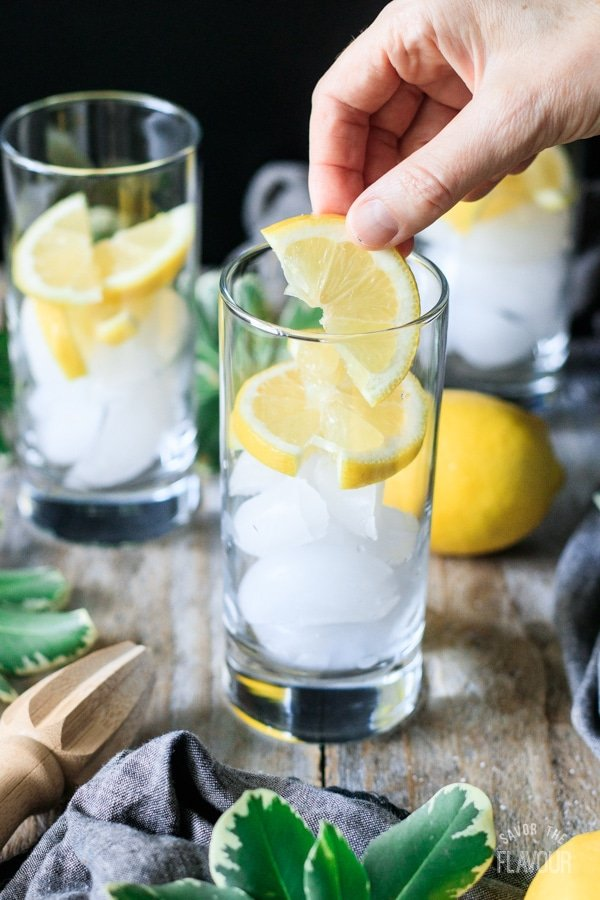 putting lemon slices into a glass