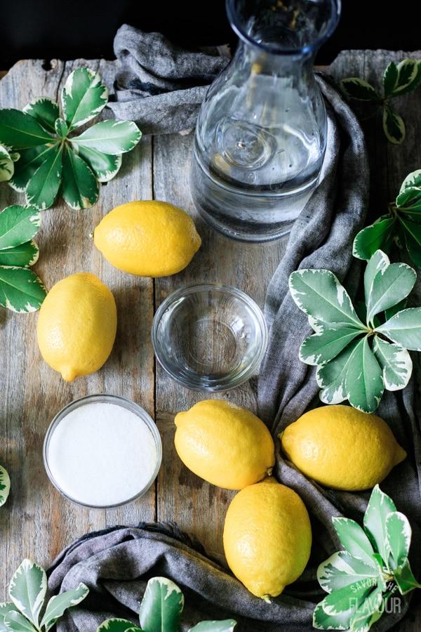 jug of water, lemons, bowl of sugar, and bowl of water