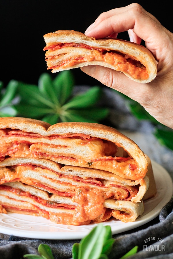 person holding a slice of pepperoni garbage bread