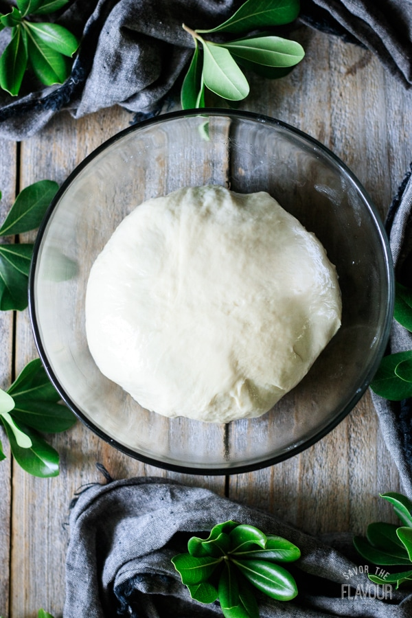 pizza dough in a glass bowl before rising