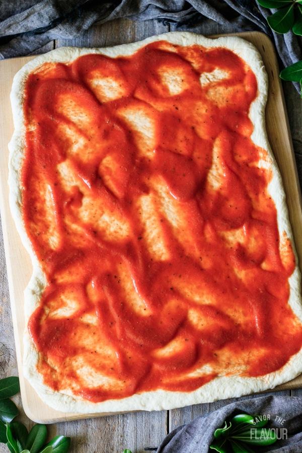 dough spread with tomato sauce