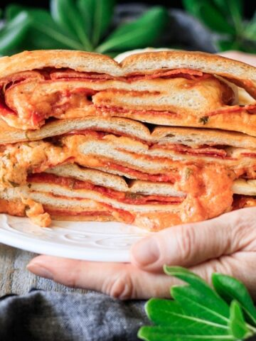 person holding a plate of pepperoni garbage bread