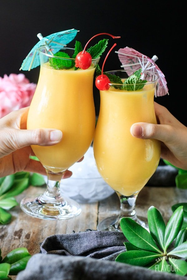 people doing a toast with two frozen mango daiquiris