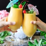 people doing a toast with two glasses of frozen mango daiquiri