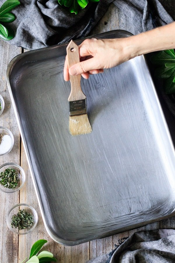 brushing a baking pan with butter