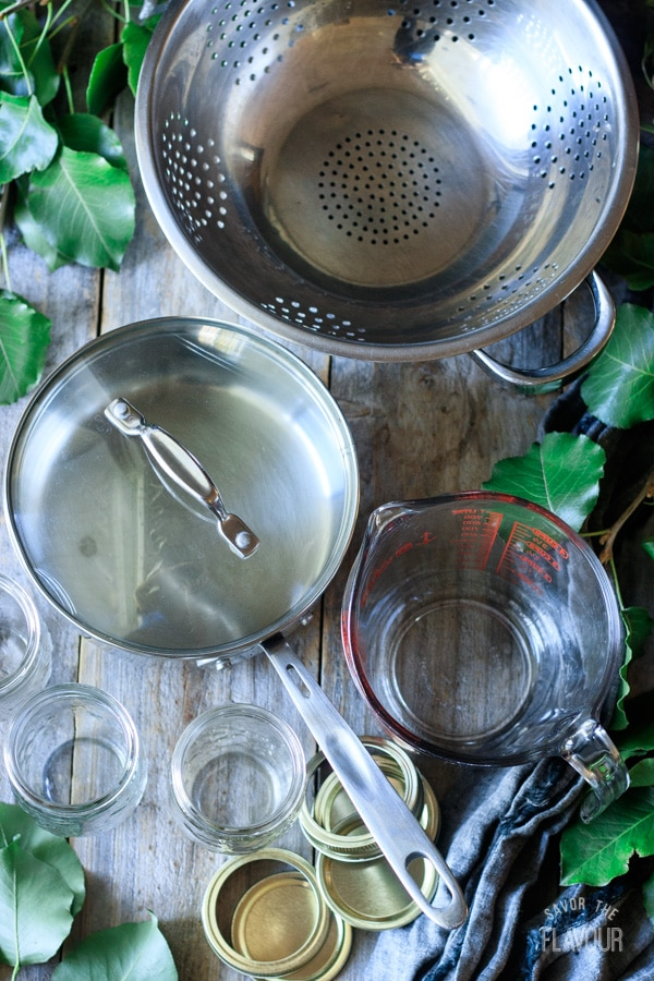 colander, pot, measuring cup, canning jars with lids