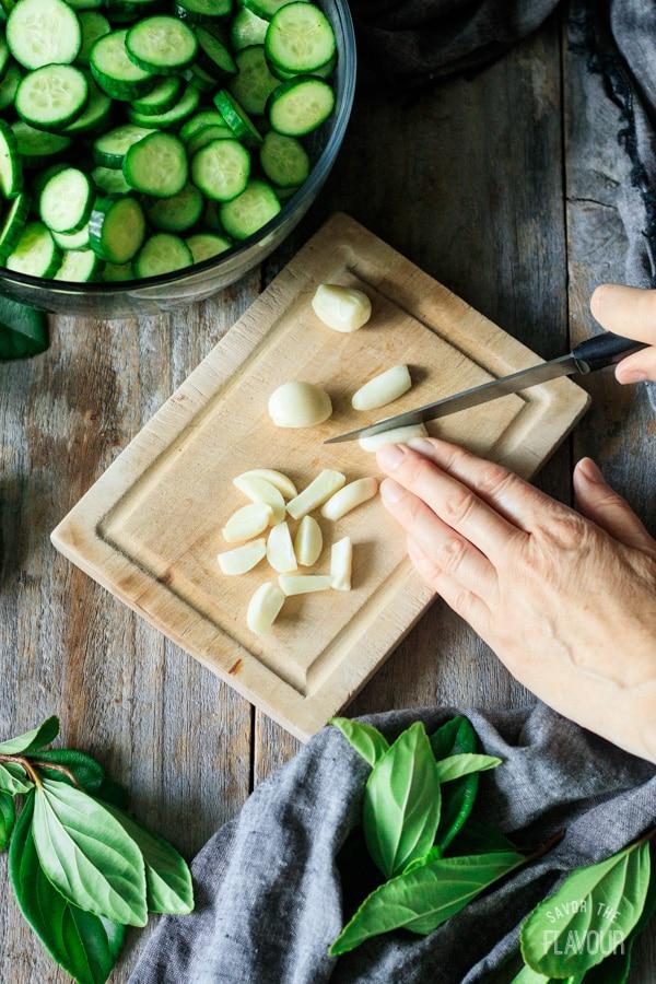 cutting garlic cloves on a wooding cutting board