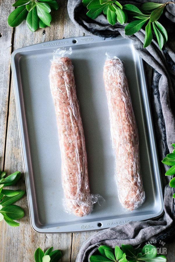 two logs of ground pork wrapped in plastic wrap