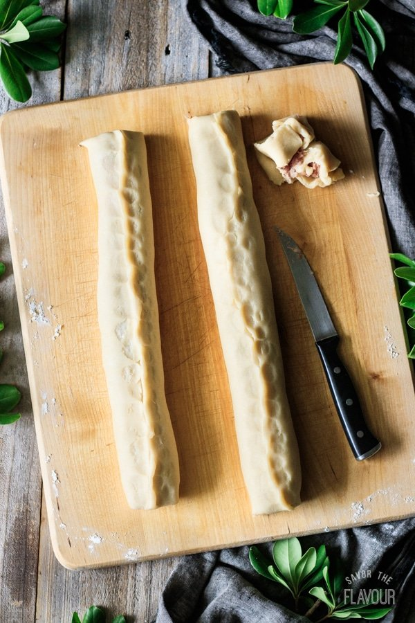 two long sausage rolls on a cutting board