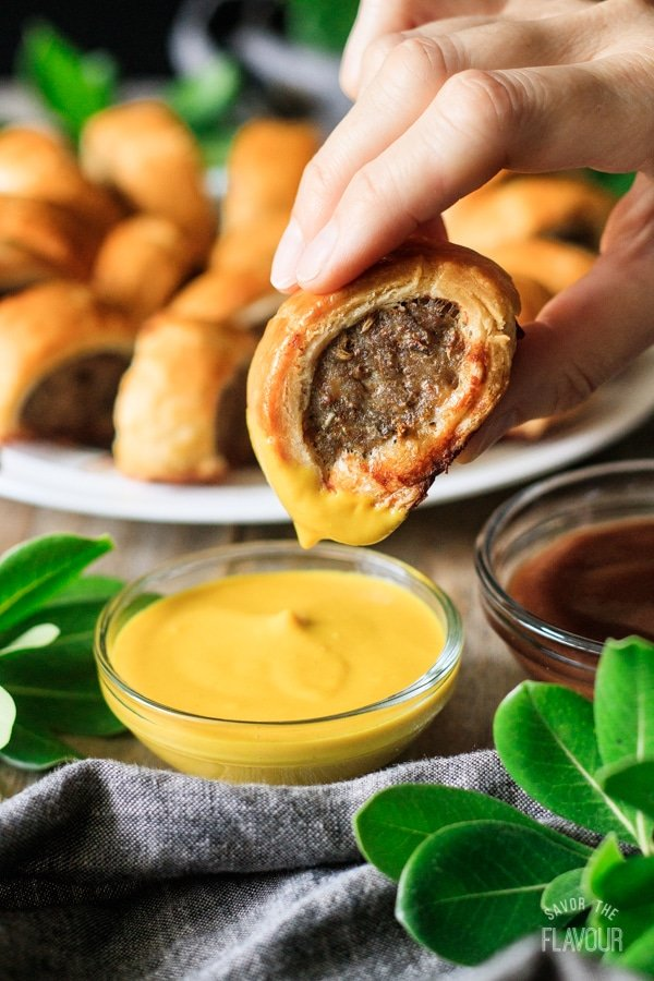 person dipping a sausage roll into mustard
