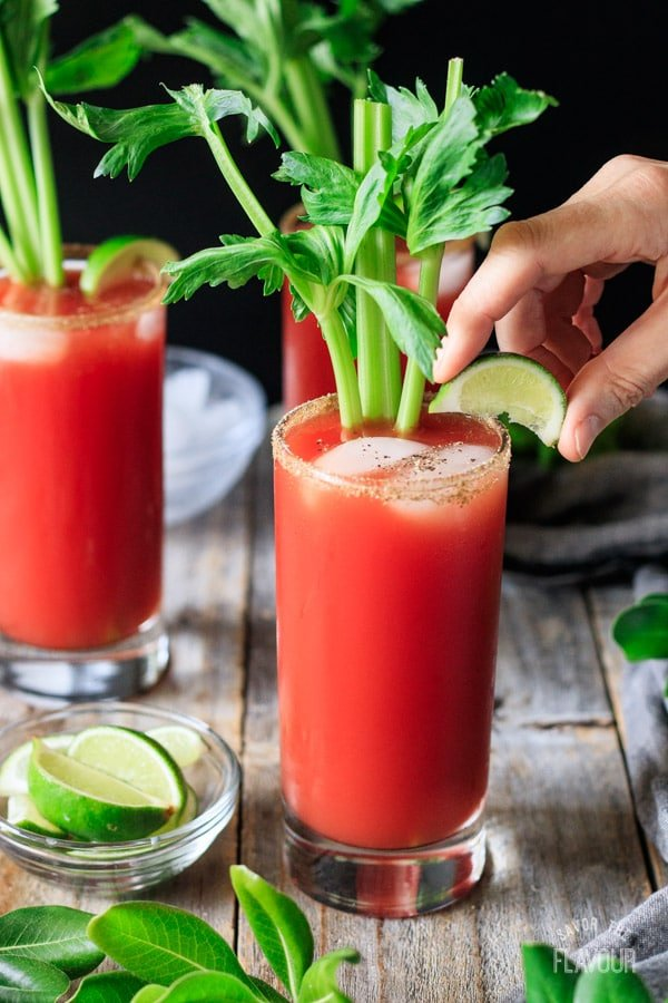 garnishing the Caesar mocktail with celery and lime