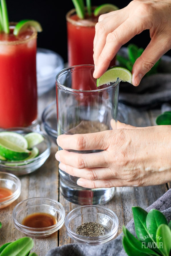 rubbing a lime wedge around the rim of the glass