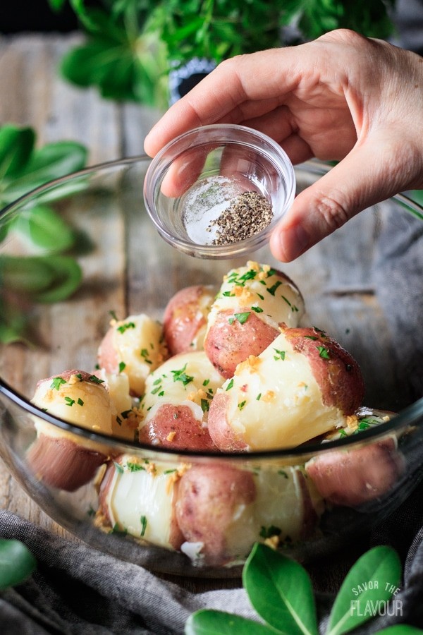 sprinkling salt and pepper on parsley potatoes
