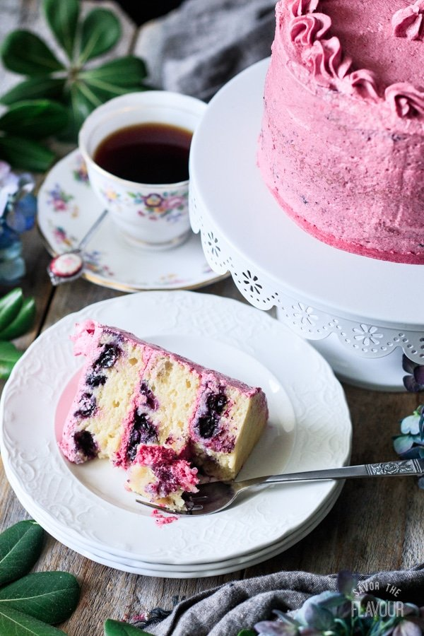 slice of lemon blueberry cake with a cup of tea