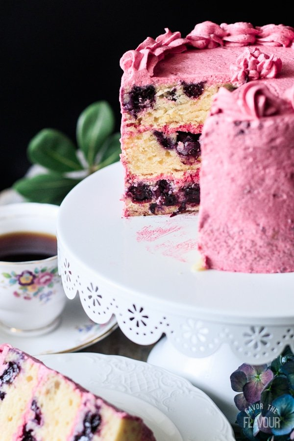 lemon blueberry cake sliced open on a cake stand