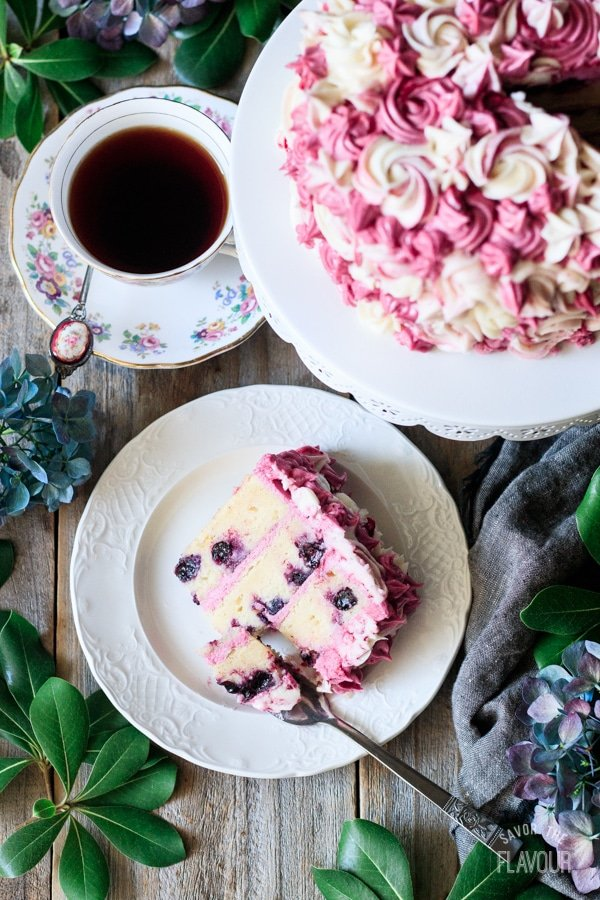top view of a slice of lemon blueberry cake with a cup of tea