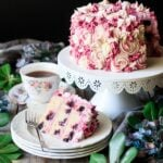 slice of lemon blueberry cake with a cup of tea and fork
