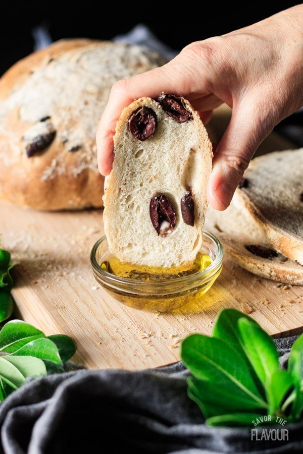 person dipping a slice of olive bread into olive oil
