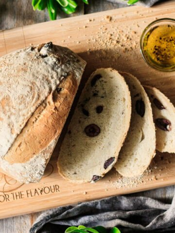loaf of olive bread on a cutting board with olive oil