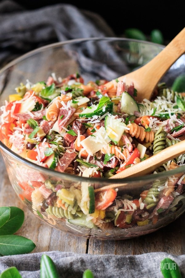 tossing Italian pasta salad with two wooden spoons